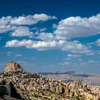 Landscape with houses in stones under sky and clouds in Cappadocia, Turkey
