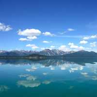 Reflections of mountains and clouds on Lake Clark