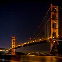 Golden Gate Bridge over the bay at night illuminated in Gold in San Francisco, California