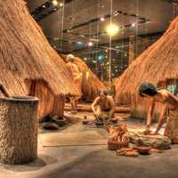 Native Americans working besides houses at Cahokia Mounds, Illinois