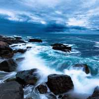 Waves of the ocean crashing on shore with skies in Acadia National Park