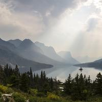Sunlight from above the clouds over the lake at Glacier National Park, Montana