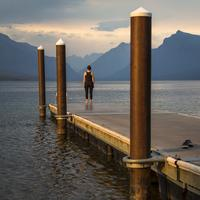 Women at the dock looking at Mountain Landscape at Glacier National Park, Montana