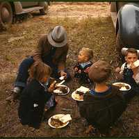 Homesteader and his children eating barbeque at the New Mexico Fair