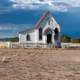 Women riding horse near a small church in Santa Fe, New Mexico