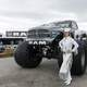 Cowgirl dressed in white standing next to monster truck in Texas