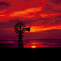 Windmill in the landscape with red skies in Texas