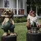 Two troll statues in front of a house in Mount Horeb