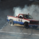 Red, white, and blue Truck burning rubber while drifting