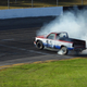 Smoke from tires from truck rallying around track