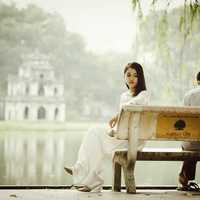 Couple sitting on a bench at Ho Guom at Hanoi, Vietnam
